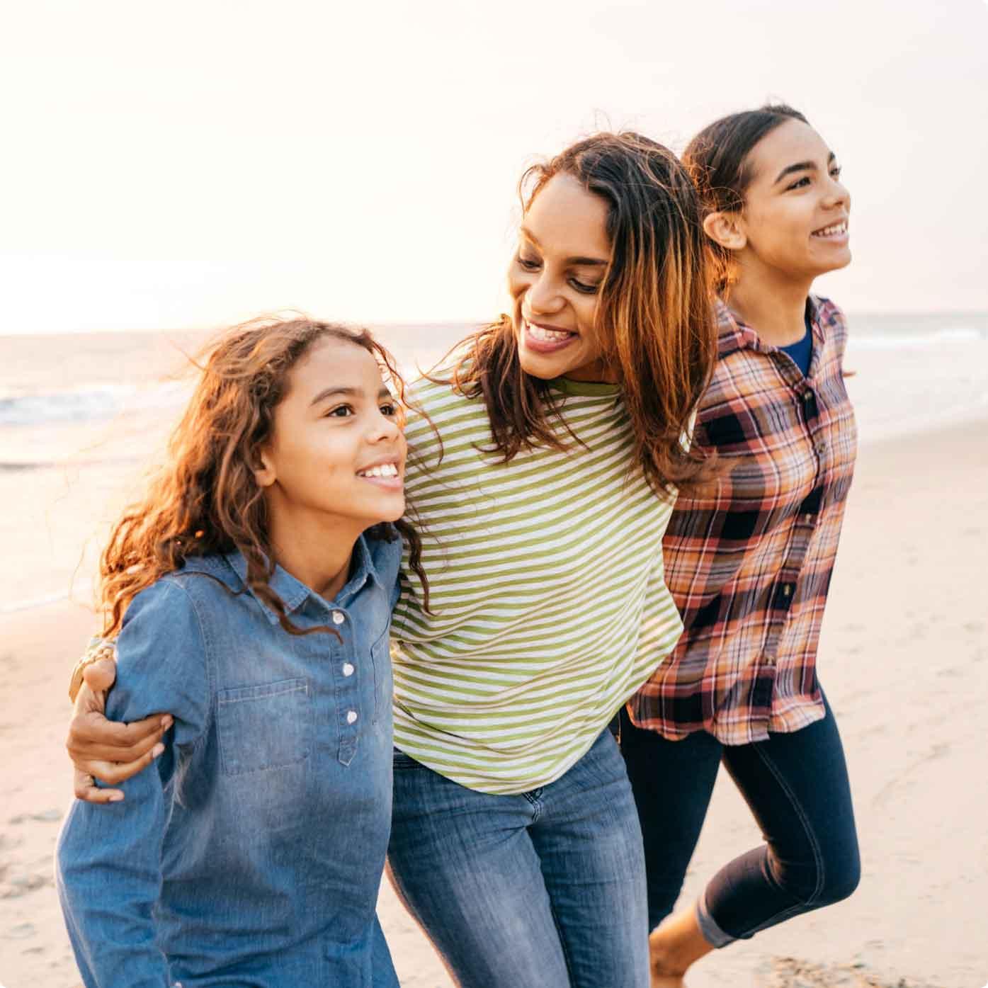 Three happy female friends strolling on the beach