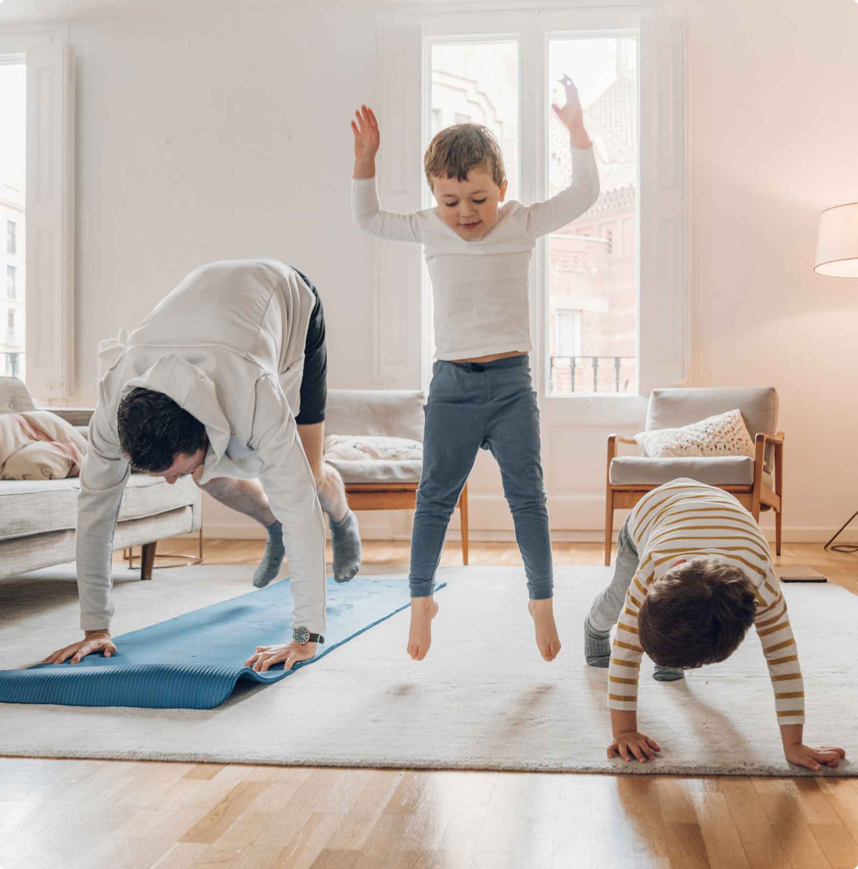 Father and sons exercising together in their living room