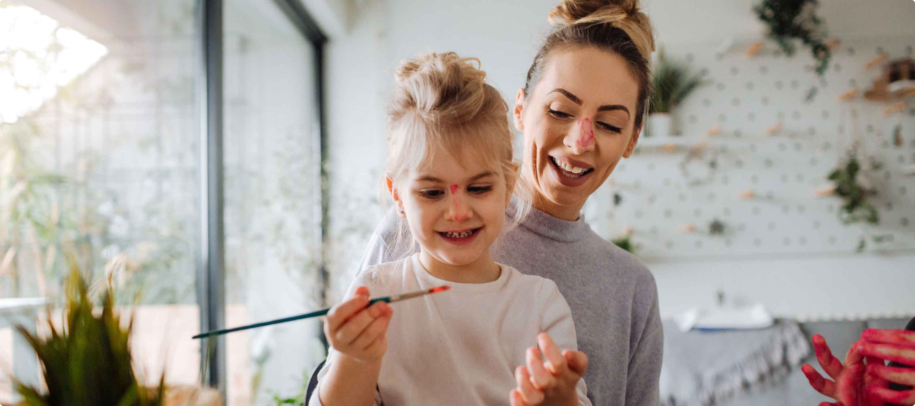 Mother and daughter having fun with a paintbrush and paint on both of their noses