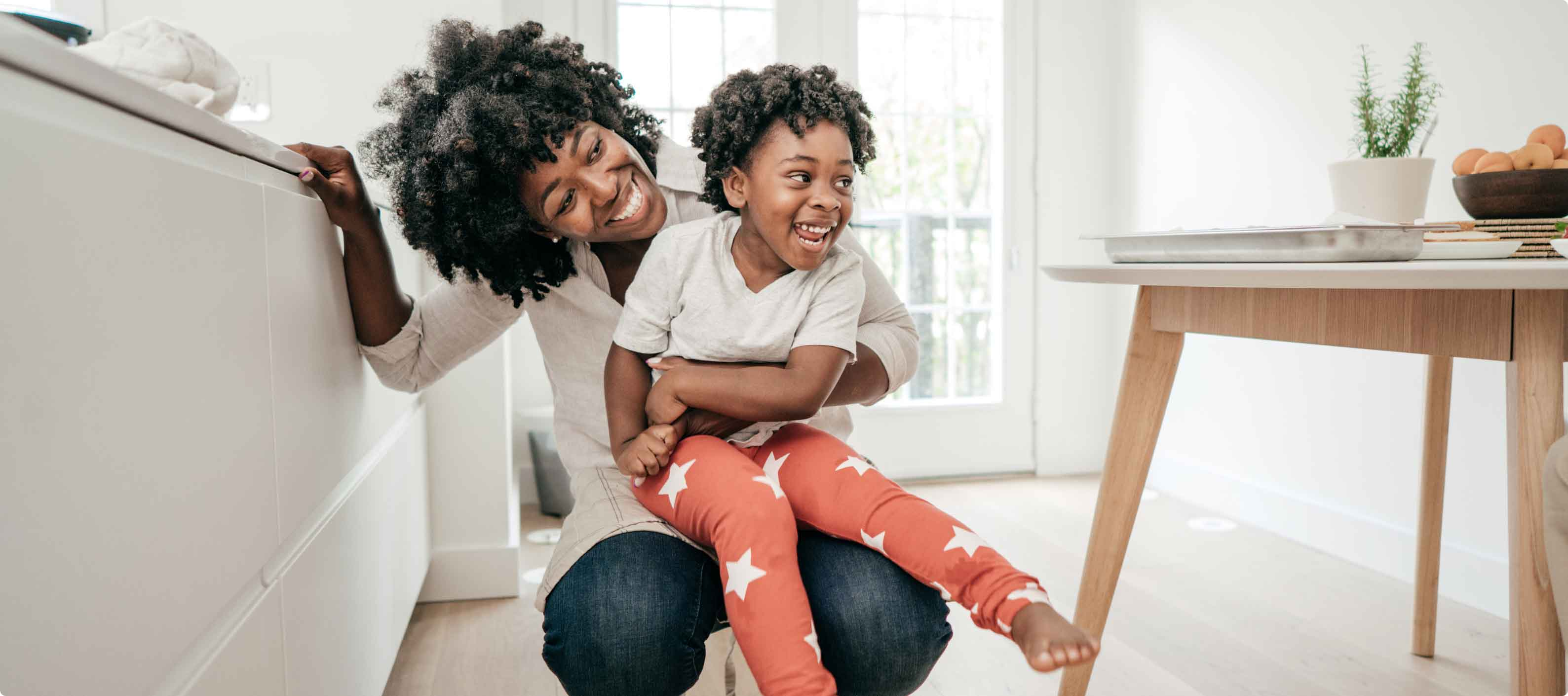 Affectionate African American mother and daughter playing