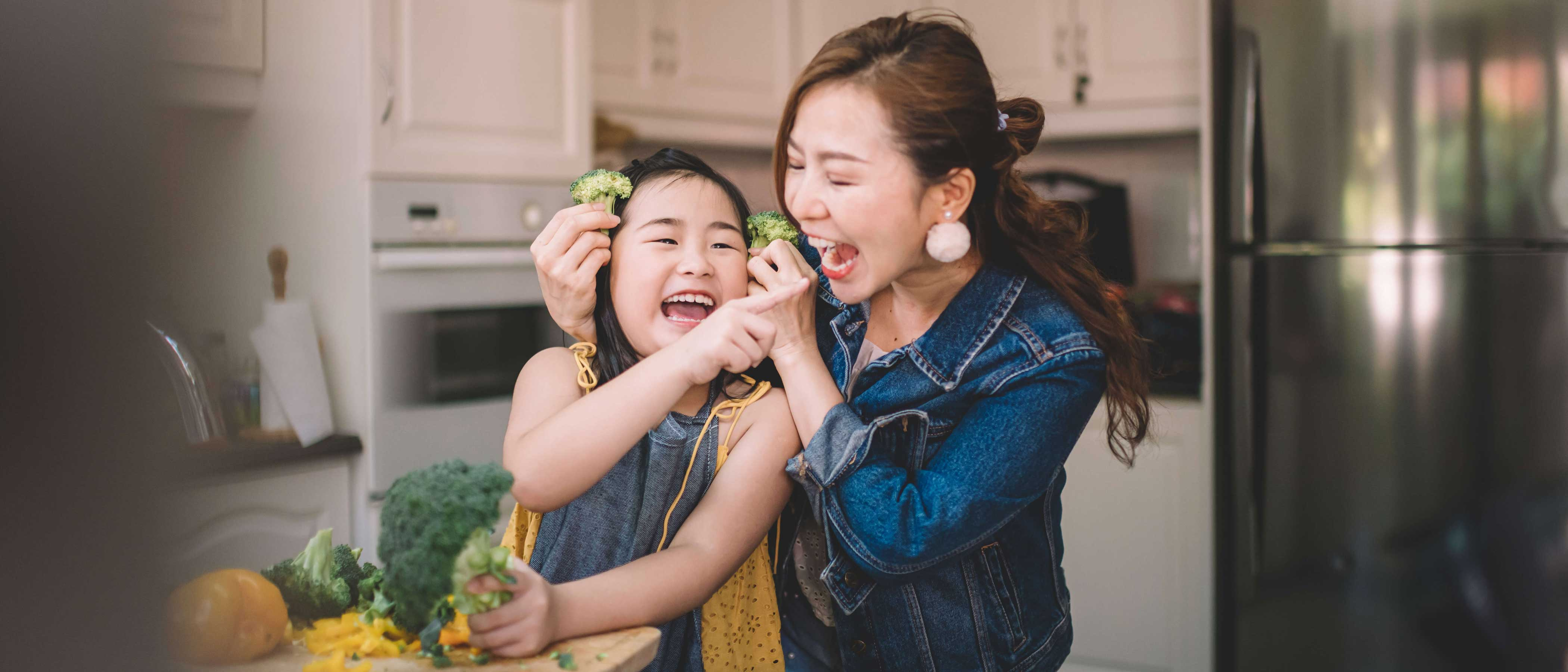 Mother and daughter in kitchen having fun while preparing food